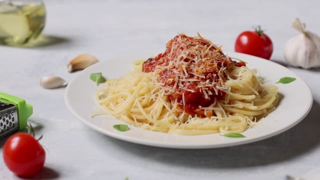 vídeos de stock e filmes b-roll de traditional italian spaghetti bolognese sprinkle with cheese on a white round plate on a white plate. ingredients for the pasta are cherry tomatoes, parmesan, garlic, olive oil, basil. - sauce