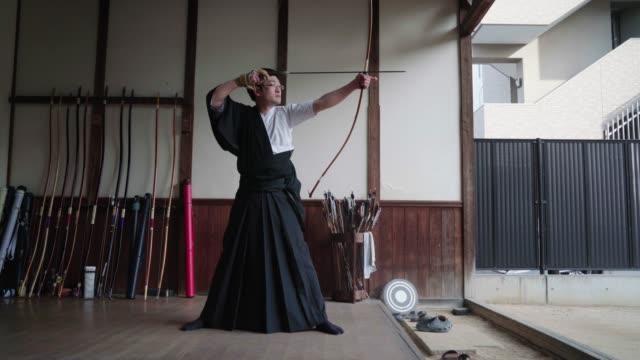 伝統的な日本の射手は彼のショットを取る - 武道点の映像素材/bロール