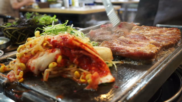 traditional korean barbecue and side dishes vegetable food. grilled on big stone plate - cultura coreana video stock e b–roll