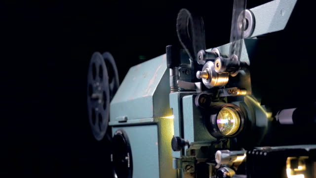 Traditional mechanical movie projector in operation. video