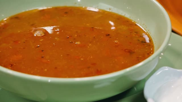 Traditional mexican bean soup with meat and cheese in a wooden bowl. Mexican food concept.