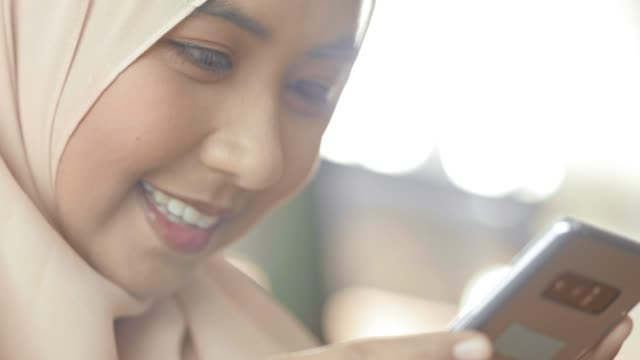 traditional muslim hijab on head typing phone - malese video stock e b–roll
