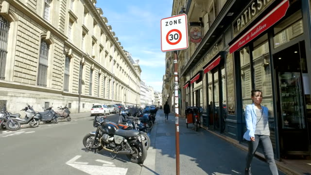 Traditional  Paris street with bakery shop and parked motorbikes and bicycles in sunny day. Cinematic steadicam shot
