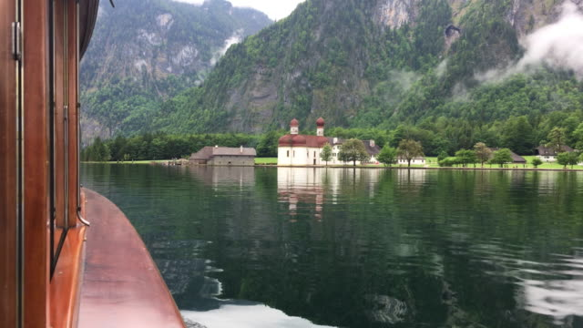 vídeos de stock e filmes b-roll de traditional passenger boat on königssee lake with tourist taking a cellphone picture of famous sankt bartholomä church in summer, bavaria, germany - bolo rei