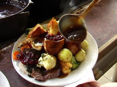 traditional roast dinner a man spoons gravy onto his roast dinner roast dinner stock videos & royalty-free footage