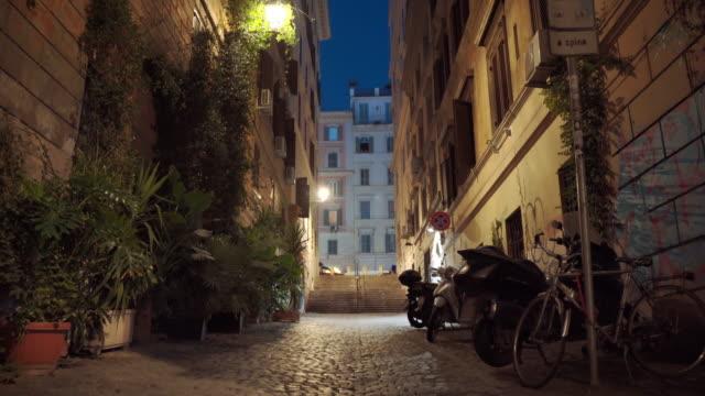 stockvideo's en b-roll-footage met traditionele romeinse straten 's nachts, hoge gebouwen en geparkeerde motorfietsen en fietsen in de buurt van de muren. straat versierd met planten en bomen, kleine trappen die leiden naar de centrale romeinse straat. verlichte romeinse straatjes met antie - raam bezoek