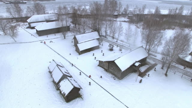 Traditional Russian village in winter Traditional Russian wooden village in winter on a snowy day. Aerial view. siberia stock videos & royalty-free footage