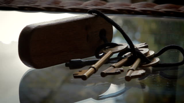 traditional set of door keys lay strewn on glass table - key ring stock videos & royalty-free footage