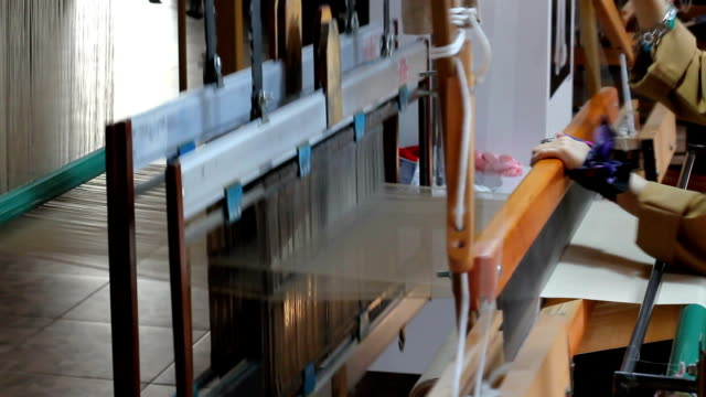 traditionellt sidentyg vävstol. gammal sidenväv vävmaskin. kvinna vävning sidentyg på vävstol. med ljud - väva bildbanksvideor och videomaterial från bakom kulisserna