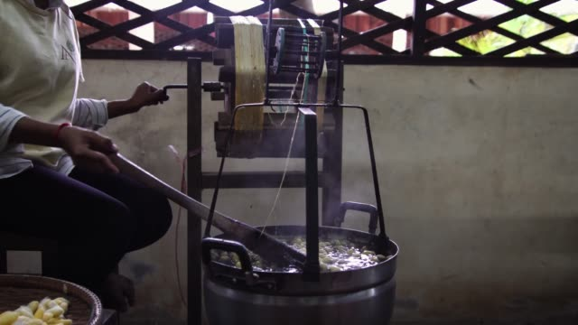 Traditional silk making. Silkworm cocoon reeling at village silk factory in Southeast Asia, Cambodia.