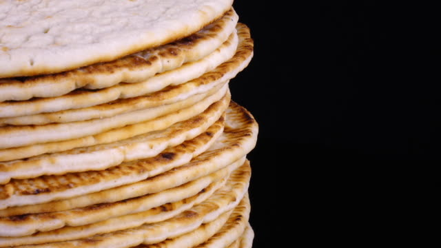 traditional tasty flat bread (lavash, pita, chapati, scone) rotating on black background - chleb pita filmów i materiałów b-roll