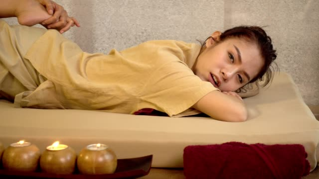 traditional thai massage, young beautiful woman relaxing in spa salon and receiving head or face massage - cultura tailandese video stock e b–roll