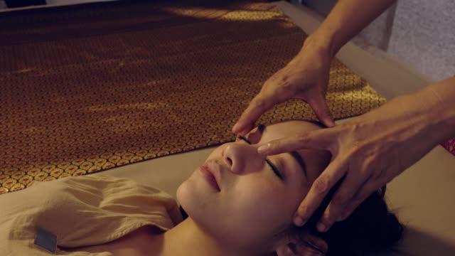 Traditional Thai Massage, Young beautiful woman relaxing in spa salon and receiving head or face massage Traditional Thai Massage, Young beautiful woman relaxing in spa salon and receiving head or face massage spa treatment stock videos & royalty-free footage