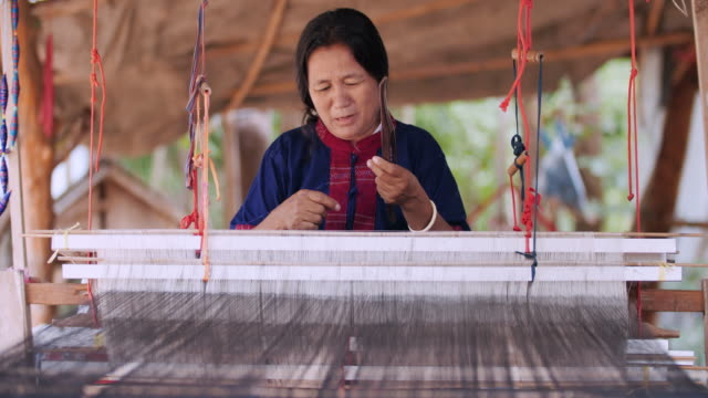 Traditional Thai textile manufacture in craft village, Old women work on wooden weaving thread machines and spin yarn creating cotton fabric.