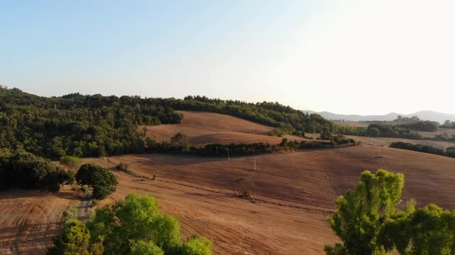 A traditional Tuscan farmhouse surrounded by working farmland, with bailed hay, lies nestled between trees growing in its garden. A lush forest surrounds the farmland in Italy