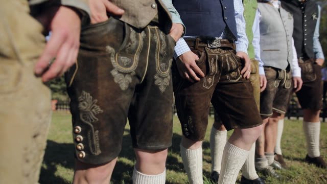 traditionally dressed bavarian men standing in a row outdoor - costume tradizionale video stock e b–roll