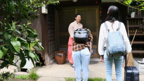 vidéos et rushes de femme japonaise traditionnellement rectifiée s'inclinant aux visiteurs à son auberge - tourisme