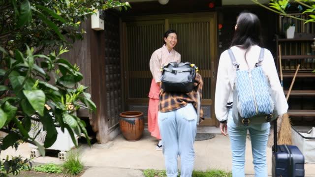 傳統打扮的日本婦女鞠躬到她的旅館的遊客 - 旅遊業 個影片檔及 b 捲影像