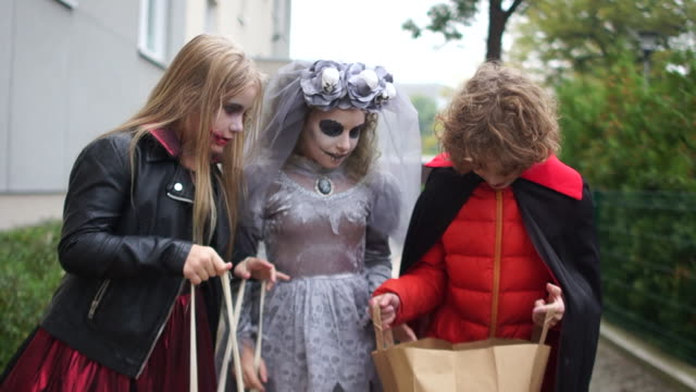 Traditions Halloween. Three teenagers in colorful costumes and bloody make-up collect sweets