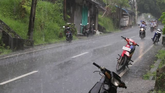 Traffic along a typical street on the road during the rain in Ubud,  Bali, Indonesia video