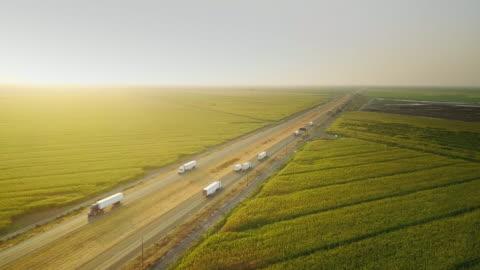 vídeos de stock e filmes b-roll de i-5 traffic between cornfields and cattle farm - aerial shot - transporte assunto