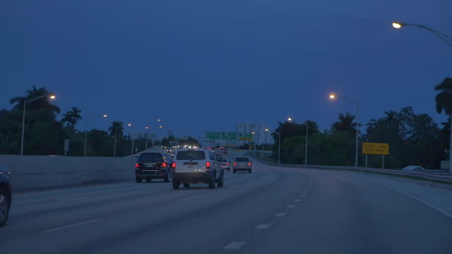 Traffic cars on an American highway going to Miami Beach or Downtown. Cloudy blue sky in the evening. Slow motion. Traffic cars on an American highway going to Miami Beach or Downtown. Cloudy blue sky in the evening. Slow motion. florida us state stock videos & royalty-free footage