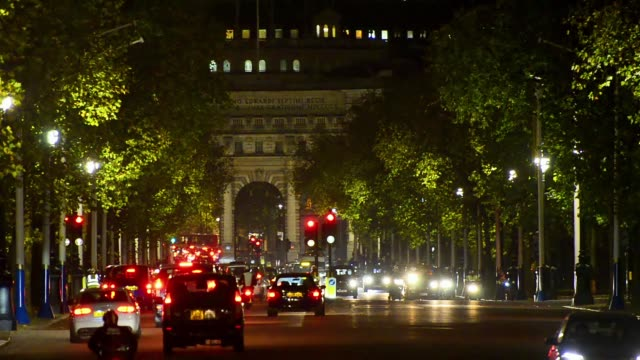 Traffic drives down The Mall towards Buckingham Palace at night video