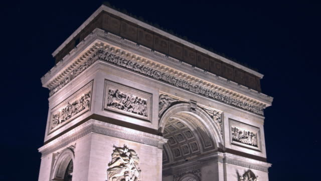 Traffic in Paris at Arc de Triomphe at night coming into focus video