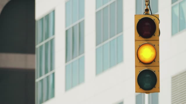 Traffic light in an American city street A traffic light in an American city crossroad street during the day. stoplight stock videos & royalty-free footage