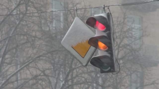 A traffic light in the snow regulates traffic during a storm. The snowfall complicated the movement of cars along the road during the cyclone. Close-up video