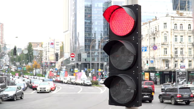 A traffic light on a city street. The green light turns on and the cars start moving. Close-up video