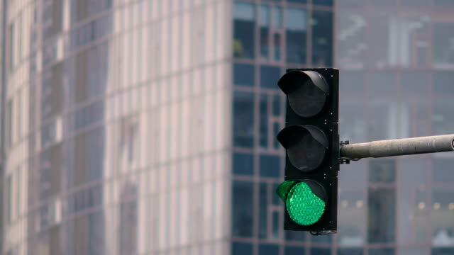 Traffic light on the background of the building. The green light is on and the red light comes on. Close-up video