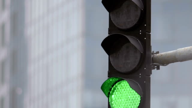 Traffic light on the background of the building. The red light is on and the green light comes on. Close-up video