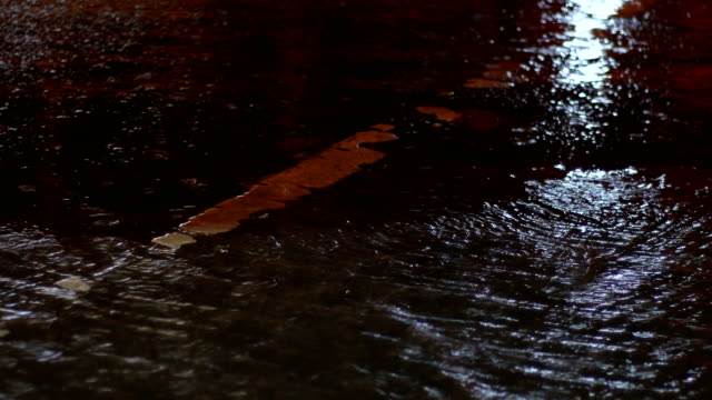 Traffic light reflect on water surface in rainy day at night video