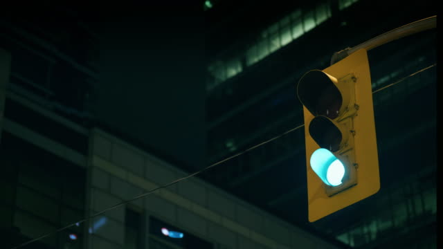 A traffic light works against a background of skyscrapers at night. Timelapse
