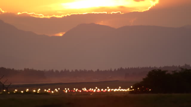 Traffic lights glowing on empty airport runway piste in countryside at sunset video