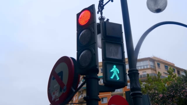 traffic lights on the street in the city of spain with red and green lights - segnale per macchine e pedoni video stock e b–roll