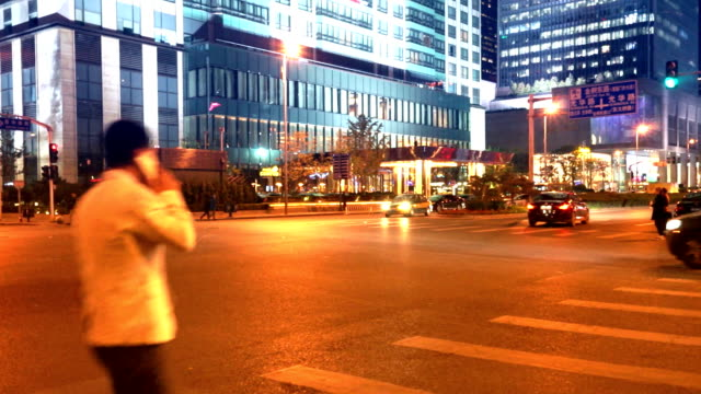 traffic on city road and modern building at night in beijing video