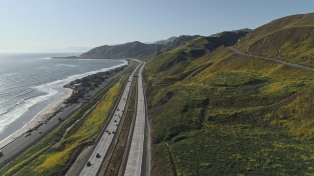 Traffic on Scenic Ventura Highway 101 along the Pacific coast nearby Emma Wood State Beach and Solimar, California, USA. Drone video with the descending camera motion. - vídeo