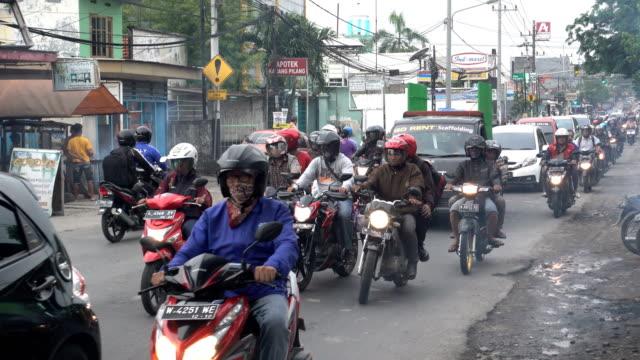 vidéos et rushes de circulation sur la route pendant l'heure de pointe à surabaya, l'île de java, indonésie - indonésie