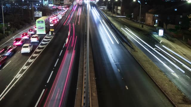 4k traffic timelapse with trailing red and white lights in the night on busy motorway/highway - droga wielopasmowa filmów i materiałów b-roll
