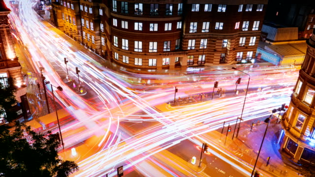 Traffic trails timelapse, London, England, UK Wide angle aerial view of traffic trails on a busy juncture in London, England, UK traffic time lapse stock videos & royalty-free footage
