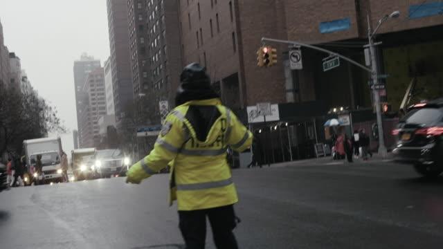 il direttore del traffico guida le auto sulla strada della città - polizia video stock e b–roll