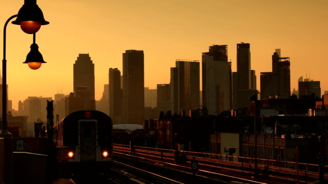Train Arrival at Sunset Subway train arriving into the station during sunset with the urban skyline in the background in Queens, New York City. subway platform stock videos & royalty-free footage