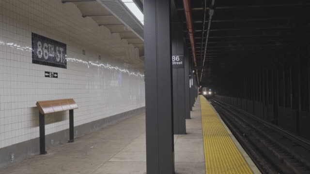 A train arriving at the 64th Street Trainstation train station deserted because of COVID-19 Coronavirus outbreak. New York City, USA. - vídeo