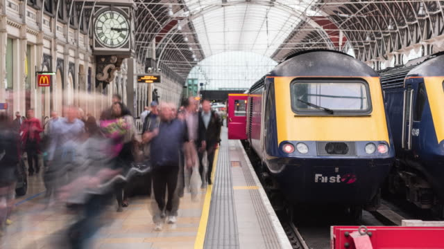 Train arriving with commuters time lapse 4K color time lapse footage of a commuter train arriving at railroad platform with passengers going out. railroad station platform stock videos & royalty-free footage