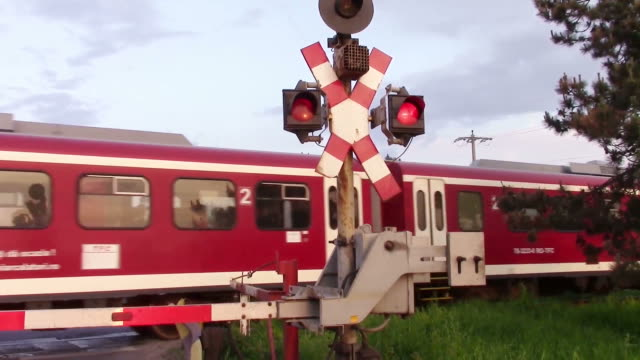 Train barrier rising after passenger train has passed, allowing road traffic to resume, at sunset video