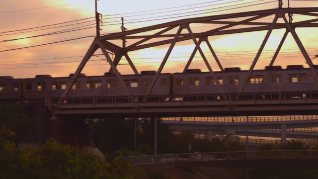 A train bathed in the sunset across a railway bridge in the suburbs of Yokohama A train bathed in the sunset across a railway bridge in the suburbs of Yokohama sunset to night time lapse stock videos & royalty-free footage