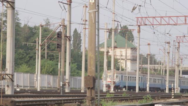Zug zum Bahnhof mit Passanten, die von vielen Hochspannungs-Türme Kabel und Leitungen an industriellen Eisenbahn Sonnentag in Kiew – Video