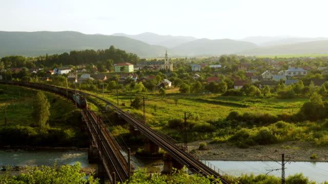tåg som går förbi bron genom bergsbyn upplyst av strålar av solnedgången - karpaterna tåg bildbanksvideor och videomaterial från bakom kulisserna
